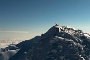 Skiers gaze over clouds from top of a mountain